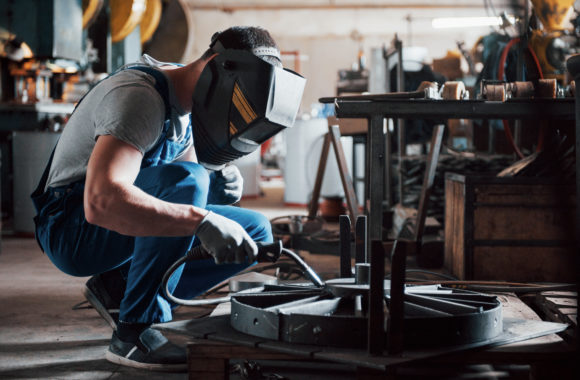 Portrait of a young worker at a large metalworking plant. The welder engineer works in a protective mask